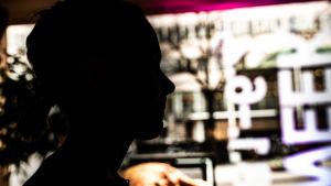 En anonym bild (helsvart profil) av en kvinna, med stora fönster, universitetsmiljö, i bakgrunden.