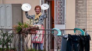 Kvinna deltar i tacksamhets- och glädjeyttring med kastrullock som cymbaler på en balkong i Rom 13.3. 2020