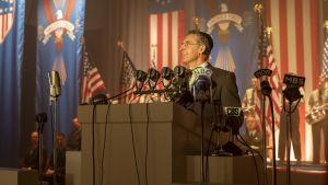 Skådespelaren John Turturro ur en scen från miniserienThe Plot Against America.Han står på ett podium inför massa mikrofoner och i bakgrunden syns amerikanska flaggor.
