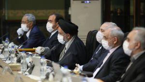 Den iranska regeringen sammanträder. Alla ministrar är iförda ansiktsmasker