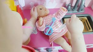 Barnet leker att hon ger spruta åt en docka.