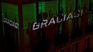 """""""Gracias"""" (""""Tack"""") reflekteras på en byggnad i Barcelona 21.3.2020. Männiksor går varje dag till sina fönster och balkonger för att tacka hälsovårdspersonal"""