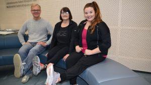 Lääkäri Harri Helajärvi, Taru Lindstedt ja fysioterapeutti Saija Kultala tekevät jumppaa sohvalla.
