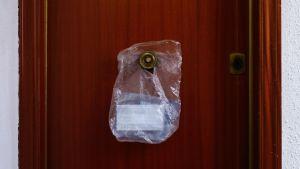 En påse som innehåller en skyddsmask hänger på dörren till en bostad för äldre i L'Hospitalet del Llobregat nära Barcelona. 18.3.2020