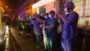 Madridilaisen sairaalan henkilökunta tervehtii suosiotaan osoittavia kansalaisia. Espanjalaisille on viime aikoina tullut tavaksi osoittaa iltaisin parvekkeilla suosiotaan koronavirusta vastaan taisteleville sairaaloiden työntekijöille.