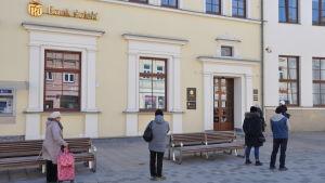Kö utanför en bank i Lublin. Alla håller rejält avstånd till varandra