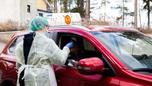 Sjukskötare i skyddsdräkt tar ett snabbtest av en person i en röd bil.