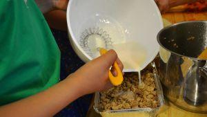 Ett barn slår vaniljsås över en kaka i form.
