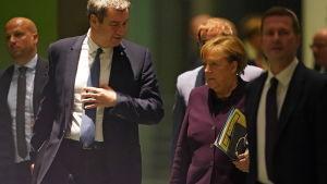 Söder, iklädd kostym, går bredvid Merkel i vinröd kavaj.