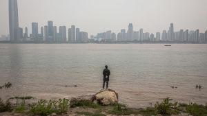 En man vid floden Yangtze tittar på staden Wuhan, Kina. 3.4.2020