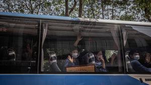Sjukvårdare från provisnen Shandong vinkar från en buss då de åker hem från Wuhan 6.4.2020