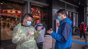 En kontrollant kollar via en mobilapplikation hälsotillståndet hos en man i ett köpcenter i Wuhan 31.3.2020.