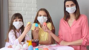 Mamma och två flickor, alla i munskydd, håller upp påskägg de målat