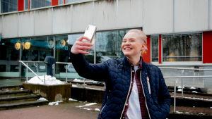 Nadine Baarman poserar i selfie-ställning utanför Yles studiohus.