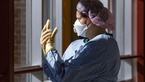En sjukskötare i skyddsutrustning står vid ett fönster.
