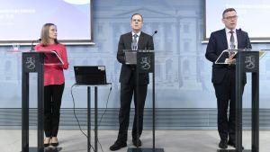 Tre personer står framför talarpodier under en presskonferens.