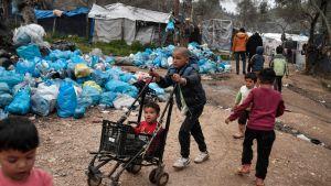 Ett barn knuffar ett mindre barn i en kärra, i bakgrunden tältläger och soppåsar.