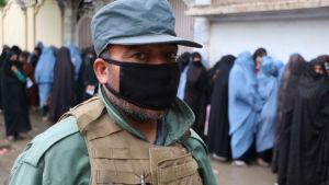 En vakt i ansiktsmask står framför kvinnor som köar för att få mathjälp