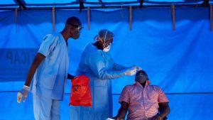 Sjukvårdare coronatestar en man i en klinik i ett tält Sydsudan