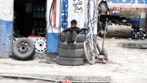 En pojke sitter på en hög bildäck utanför en verkstad i Jemens huvudstad Sanaa