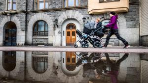 Två unga mammor med barnvagn promenerar i Åbo invid en stor vattenpöl