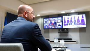 Rårdsordföranden Charles Michel framför en tv-skärm