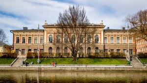 Några människor sitter på kajkanten invid Åbo stadshus.