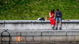 Ett par sitter vid kajkanten vid Aura å och tittar på sina mobiltelefoner.