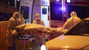 valkosiiin suojapukuihin pukeutuneet lääkintähenkilöt siirtävät potilasta paareilla ambulanssiin