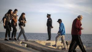 En polis i skyddsmask övervakade flanörer vid en strand utanför Aten på lördagen.