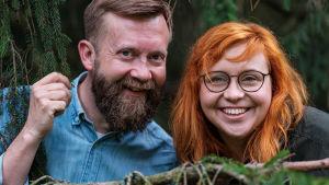 Närbild av Annika Ljungberg och Joakim Lax på en sten i skogen.