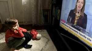 Litet barn sitter på golvet i hemmiljö, tittar på Li Andersson i regeringens coronainfo på tv.