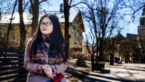 Asiatisk ung kvinna i glasögon sitter på parkbänk mellan trähus klädd i rosa kappa och grann halsduk.