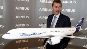 Airbus vd Guillaume Faury står bredvid en modell av ett Airbus A350-900-plan