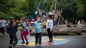 En pojke med Downs Syndrom leker på en skolgård.
