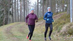 Två damer kommer löpande på en skogsstig.