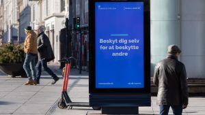 Skylt på gata i Köpenhamn uppmanar danskarna att skydda sig själv för att skydda andra.