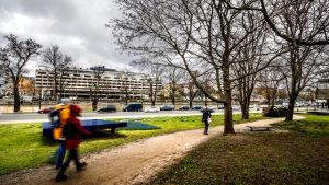 Fotgängare promenerar längs ett gångstråk invid Aura å