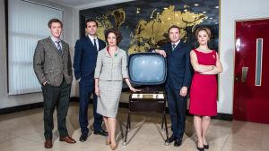 Sarjan hahmot seisovat isossa huoneessa vanhan television ympärillä.