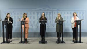Li Andersson, Katri Kulmuni, Sanna Marin, Maria Ohisalo och Anna-Maja Henriksson på rad under en presskonferens.