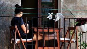 Nainen istuu parvekkeella kuulokkeet korvissaan, suojahansikkaat riippuvat pyykkinarulla