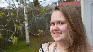 Joanna Slama, en flicka med långt, ljust hår står vid ett blommande träd.