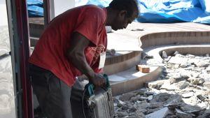 En arbetare utan hörselskydd använder en gatuborr