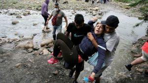 Två män bär en gammal kvinna över gränsfloden mellan Venezuela och Colombia