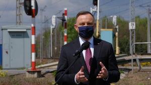 Presidentti Andrzej Duda kasvosuojus naamallaan.