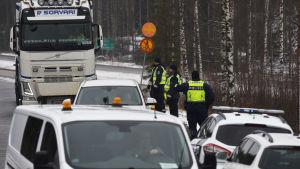 Poliser och bilar vid gränsen till Nyland.