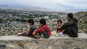 Barn sitter på en mur och tittar ut över Kabul 17.5.2020