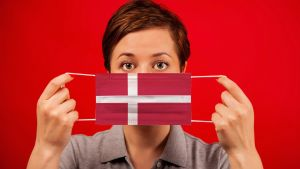 Kvinna framför röd bakgrund med munskydd, i danska flaggans färger.