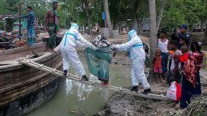 Två hjälparbetare iklädda skyddsutrustning mot coronaviruset hälper en person att ta om bord sig på en båt. De har en spång från flodbanken till båten.