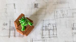 leksaksgroda sitter på små tegelstenar på handritad bostadsriting